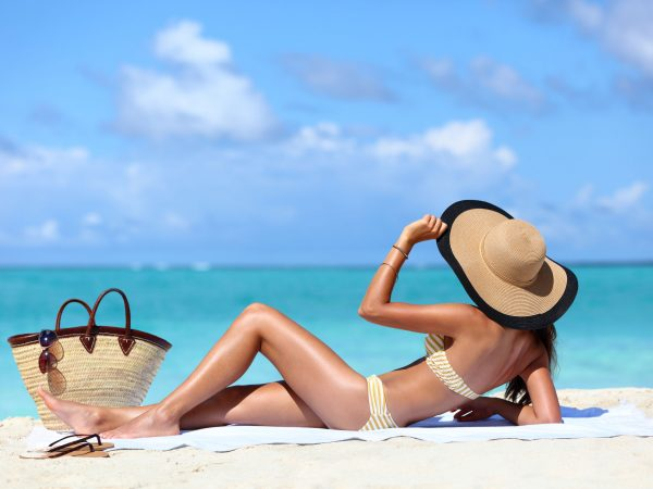 53759130 – sexy bikini woman tanning relaxing on beach. suntan concept. unrecognizable female adult from the back lying down with straw hat sunbathing under the tropical sun on caribbean vacation.